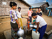 05 NOVEMBER 2014 - SITTWE, RAKHINE, MYANMAR: Women draw cooking water from a community well in a Rohingya Muslim IDP camp near Sittwe. After sectarian violence devastated Rohingya communities and left hundreds of Rohingya dead in 2012, the government of Myanmar forced more than 140,000 Rohingya Muslims who used to live in and around Sittwe, Myanmar, into squalid Internal Displaced Persons camps. The government says the Rohingya are not Burmese citizens, that they are illegal immigrants from Bangladesh. The Bangladesh government says the Rohingya are Burmese and the Rohingya insist that they have lived in Burma for generations. The camps are about 20 minutes from Sittwe but the Rohingya who live in the camps are not allowed to leave without government permission. They are not allowed to work outside the camps, they are not allowed to go to Sittwe to use the hospital, go to school or do business. The camps have no electricity. Water is delivered through community wells. There are small schools funded by NOGs in the camps and a few private clinics but medical care is costly and not reliable.   PHOTO BY JACK KURTZ