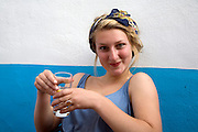 Model released portrait of teenage girl sitting holding a drink puling a silly face, UK