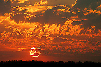 Boiling red clouds above setting sun create a stunning prairie sunset, near Qu'Appelle Valley Saskatchewan