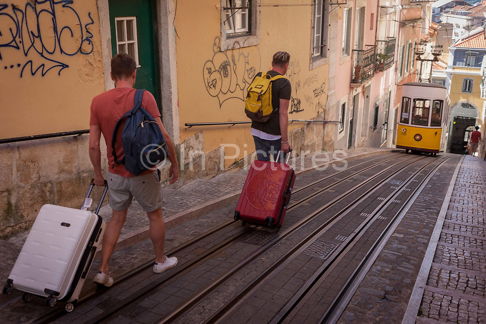Two tourists walk downhill with their baggage towards one of the two cars of the funicular railway climbing the steep gradient of on Rua de Bica de Duarte Belo Elevador da Bica, on 13th July 2016, in Lisbon, Portugal. The mechanical motor of the elevator was installed in 1890, but the lift only began functioning on 28 June 1892, after a couple of years of tests. The Bica Funicular is a funicular railway line in the civil parish of Misericórdia, in the municipality of Lisbon, Portugal. It connects the Rua de São Paulo with Calçada do Combro/Rua do Loreto, operated by Carris.