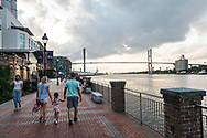 Savannah, Georgia, USA - July 26, 2021: A family holds hands as they walk beside the Savannah River at the Plant Riverside District in Savannah.