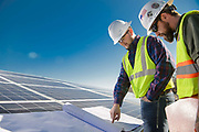 Utility workers examining engineering drawerings at a solar field