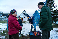Fran and Tink Taylor get warmed up by the fire as the sun sets during Prescott Farm Environmental Center's  Winter Solstice party on Saturday afternoon.  (Karen Bobotas/for the Laconia Daily Sun)
