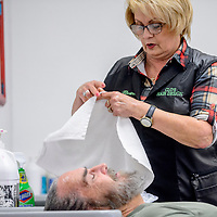 Grants mayor Modie Hicks soaks his hair as Clorinda Brito unfolds a towel at Clo's Hair Design in Grants Thursday. Hicks had his hair cut after a fundraiser to benefit the Marine ROTC drill team trip to a national competition.