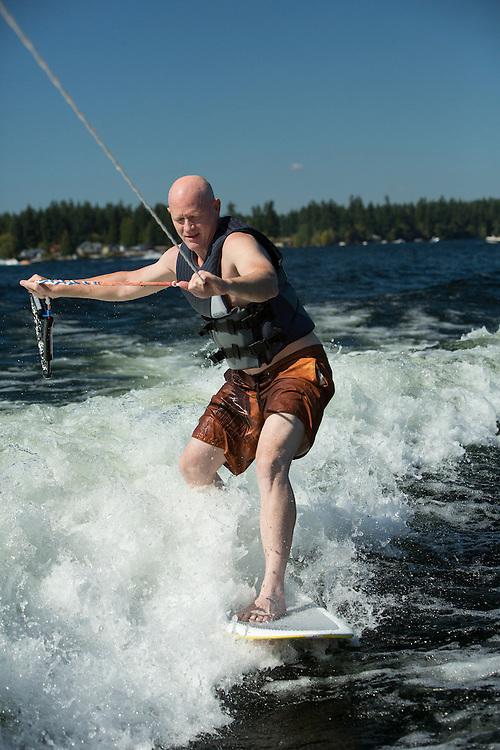 United States, Washington, Lake Sawyer,man surfing behind motorboat.  MR