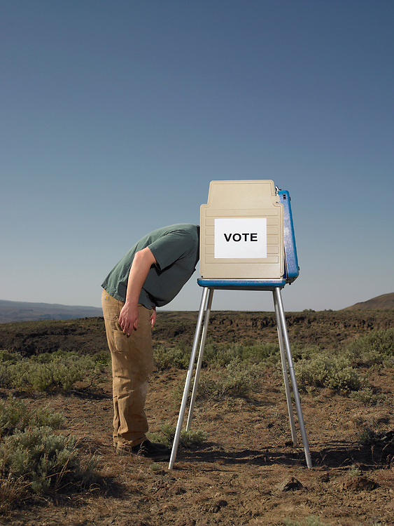 Man sticking head in voting booth outdoors.