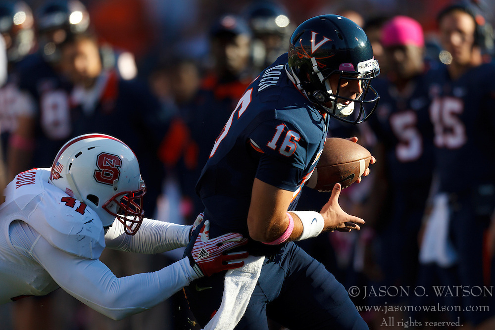 Oct 22, 2011; Charlottesville VA, USA;  Virginia Cavaliers quarterback Michael Rocco (16) is chased out of bounds by North Carolina State Wolfpack linebacker Dwayne Maddox (41) during the second quarter at the Scott Stadium.  Mandatory Credit: Jason O. Watson-US PRESSWIRE