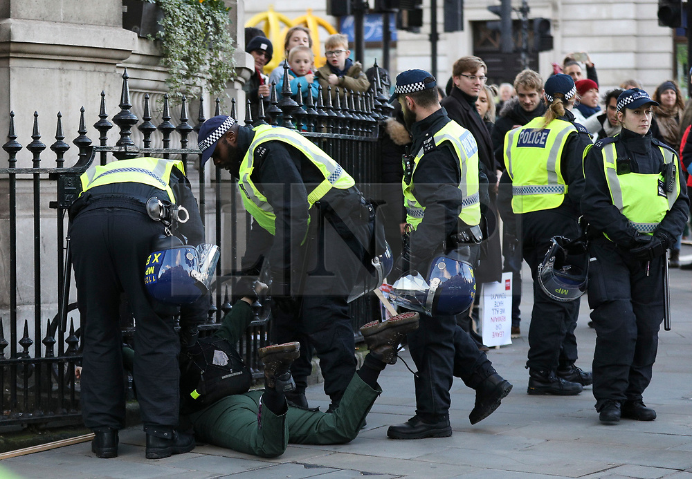 © Licensed to London News Pictures. 09/12/2018. London, UK. A woman is detained by police as Anti-fascist protestors take part in a counter demonstration against Pro-Brexit protesters at the 'Brexit Betrayal' march in central London, led by far-right activist Tommy Robinson. Prime Minister Theresa May's proposed Brexit deal will be voted on by MPs in the coming week. Photo credit: Tom Nicholson/LNP