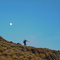 The moon rises above a photographer in California's rugged White Mountains above Bishop, California.