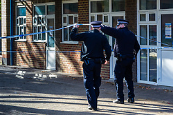 Police officers enter the cordon following the murder on October 17th of Ian Tomlin, 46, at the sprawling high-rise Doddington estate in Battersea, South London . Battersea, London, October 18 2018.