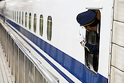Shinkansen, a train conductor make the sign to verifie every passengers get on the train befor closing doors.