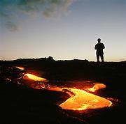 A man standing beside a lava flow in Hawaii Volcanoes National Park, Hawaii, USA