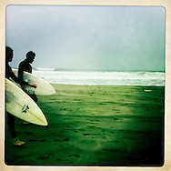 Surfers walk down a cold, Outer Sunset beach in San Francisco.
