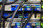 Nederland, Nijmegen, 4-12-2016Kabels steken achterin servers en netwerkswitches in de computerruimte van een groot bedrijf.Foto: Flip Franssen