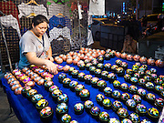 26 MAY 2016 - BANGKOK, THAILAND: A woman who sells Thai nick-nacks in the Silom Road night market sets out her merchandise. The night market on Silom Road, close to Bangkok's famous Patpong tourist area, is being closed by the Bangkok municipal government. Vendors have been told they have to leave the sidewalk on Silom Road by the end of May, 2016. The market is the latest street market being shut down by city officials as a part of the government's plan to clean up Bangkok. The Silom Road night market sells mostly tourist oriented clothes, inexpensive Thai art, and bootleg movies on DVD.       PHOTO BY JACK KURTZ
