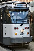 A male Belgium De Lijn tram driver drives the tram full of passengers along the 24 route towards Sint-Pieterssation in the centre of Ghent, Belgium.