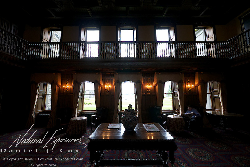 A gentleman catches up on the news reading a news paper in the Ashford Castle, Ireland.