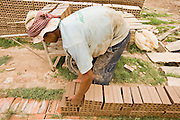 30 JUNE 2006 - PHNOM PENH, CAMBODIA: A worker stacks bricks in the sun to dry them before putting them into a kiln at a brick factory in Phnom Penh, Cambodia. According the United Nations Food and Agricultural Organization, there are more than 70 brick factories in Phnom Penh and its environs. Environmentalists are concerned that the factories, most of which burn wood in their kilns, contribute to deforestation in Cambodia. They are encouraging factory owners to switch to burning rice husks, as brick kilns in neighboring Vietnam do. The brick factories are kept busy feeding Phnom Penh's nearly insatiable appetite for building materials as the city is in the midst of a building boom brought by on economic development and the need for new office complexes and tourist hotels.   Photo by Jack Kurtz / ZUMA Press