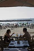 A couple dine at a beach restaurant, Tel Aviv, Israel
