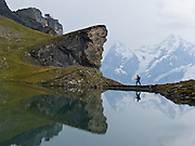 """A hiker and peaks of Eiger and Mönch reflect in Grauseeli lake below Birg, the midway station on the Schilthorn cable car in the Berner Oberland, Switzerland, the Alps, Europe. The Bernese Highlands are the upper part of Bern Canton. UNESCO lists """"Swiss Alps Jungfrau-Aletsch"""" as a World Heritage Area (2001, 2007)."""