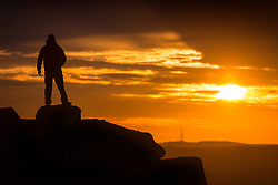 © Licensed to London News Pictures. 02/08/2017. Ilkley UK. A man stands on top of the Cow & Calf rocks at the top of Ilkley Moor in Yorkshire at sunrise this morning. Photo credit: Andrew McCaren/LNP