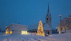 """THEMENBILD - Gemeinehaus, Weihnachtsbaum und Pfarrkirche Kals zur blauen Stunde, aufgenommen am Samstag den 5. Dezember 2020, in Osttirol. Der Winter macht sich in Teilen Österreichs mit enormen Schnee- und Regenmengen bemerkbar. Die anhaltend starken Schneefälle sowie Sturm auf den Bergen haben in Osttirol die Lawinengefahr weiter ansteigen lassen. Der Lawinenwarndienst Tirol gab für Sonntag Stufe """"5"""", also die höchste Gefahrenstufe, aus. // Community house, Christmas tree and parish church Kals at the blue haur, recorded on Saturday, December 5, 2020, in East Tyrol, taken on Sunday, December 6, 2020, in East Tyrol. The winter is making itself felt in parts of Austria with enormous amounts of snow and rain. The continuing heavy snowfall and storms on the mountains have further increased the danger of avalanches in East Tyrol. The Avalanche Warning Service Tyrol issued level """"5"""", the highest danger level, for Sunday. EXPA Pictures © 2020, PhotoCredit: EXPA/ Johann Groder"""
