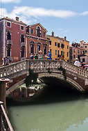 Tourists line a bridge over one the the many canals of Venice, enjoying a sunny summer day in Italy