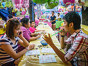 """27 NOVEMBER 2012 - BANGKOK, THAILAND:  A couple on a date in the Bingo tent at the Wat Saket Temple Fair in Bangkok. Bingo is called Bingo in Thailand. Wat Saket, popularly known as the Golden Mount or """"Phu Khao Thong,"""" is one of the most popular and oldest Buddhist temples in Bangkok. It dates to the Ayutthaya period (roughly 1350-1767 AD) and was renovated extensively when the Siamese fled Ayutthaya and established their new capitol in Bangkok. The temple holds an annual fair in November, the week of the full moon. It's one of the most popular temple fairs in Bangkok. The fair draws people from across Bangkok and spills out in the streets around the temple.   PHOTO BY JACK KURTZ"""