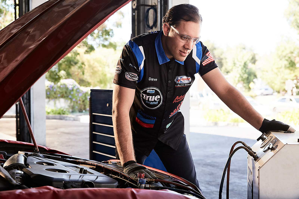 Raymond Rudolph photographs a mechanic performing air conditioning diagnostics during an advertising photoshoot for Speedee-Midas
