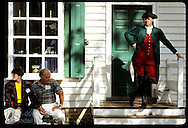 Man in period dress waits at door to admit tourists into 18th-c. building; Colonial Williamsburg. Virginia