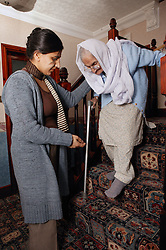 Granddaughter helping her Sikh elderly grandmother to walk down the stairs,