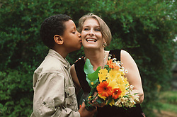 Young boy giving bunch of flowers to mother and kissing her on the cheek,