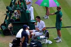 John Isner receives treatment during a medical time out on day eleven of the Wimbledon Championships at the All England Lawn Tennis and Croquet Club, Wimbledon.