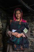 Tasfiya, 16, holds a blanket from the shelter kit in her collapsed house in Purnishadashah village, Jammu and Kashmir, India, on 24th March 2015. Tasfiya's house was destroyed in the floods forcing her family to move in with relatives. Save the Children supported the family with kitchen items, hygiene kits, food baskets, blankets, a solar powered lamp and education kits for the children. Photo by Suzanne Lee for Save the Children
