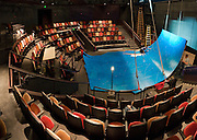Jones Playhouse interior was remodeled in 2009, shown here with a blue set for a play. Originally a storehouse and remodeled into a theatre in 1930, the Floyd and Delores Jones Playhouse (originally called the Seattle Repertory Playhouse), was the very first state sponsored theatre in the nation and was home to WPA projects and the Negro Theatre Projects, NTP (part of Federal Theatre Project, FTP). It has a thrust stage and seats 210. Located at 4045 University Way NE, Seattle, Washington.