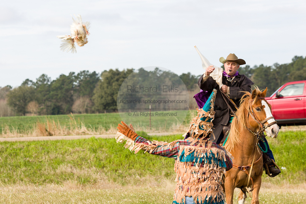 The Le Capitaine tosses a live chicken during a traditional Cajun Mardi Gras to costumed revelers during the Courir de Mardi Gras chicken run on Fat Tuesday February 17, 2015 in Eunice, Louisiana. Cajun Mardi Gras involves costumed revelers competing to catch a live chicken as they move from house to house throughout the rural community.