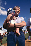 President Jimmy Carter holds the baby of friends at a softball game in Plains, Georgia. 1977 - To license this image, click on the shopping cart below -