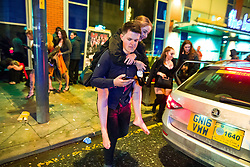 © Licensed to London News Pictures . 01/01/2018. Manchester, UK. A man gives a woman a piggy back on Withy Grove . Revellers celebrate the start of the New Year in Manchester City Centre . Photo credit: Joel Goodman/LNP