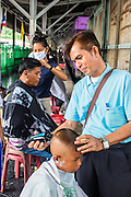 17 APRIL 2013 - BANGKOK, THAILAND:   Travelers get haircuts on a platform at Hua Lamphong Train Station in Bangkok. Songkran, the traditional Thai New Year, is the busiest time of the year for Thai domestic travel. Many people in Bangkok return to their home provinces for the holiday and some people in the provinces travel to Bangkok for the holiday. Songkran, usually a three day holiday, was five days this year because the official days on the weekend. Trains and buses coming into Bangkok were reported to be fully booked and the State Railway of Thailand added extra trains and carriages to accommodate the crowds.  PHOTO BY JACK KURTZ
