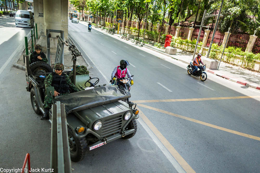 """20 MAY 2104 - BANGKOK, THAILAND: Thai soldiers at a checkpoint on Rama I Road in Bangkok after the Thai army declared martial law. The army declared martial law throughout Thailand in response to growing political tensions between anti-government protests led by Suthep Thaugsuban and pro-government protests led by the """"Red Shirts"""" who support ousted Prime Minister Yingluck Shinawatra. Despite the declaration of martial law, daily life went on in Bangkok in a normal fashion. There were small isolated protests against martial law, which some Thais called a coup, but there was no violence.   PHOTO BY JACK KURTZ"""