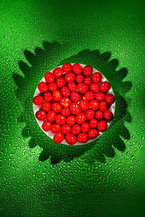 Sweetcherrys on white plate and green wet glass with strong shadows