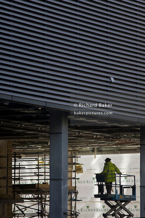 A workman operates a scissor lift beneath the large ceiling of a new development in Fenchurch Street, the heart of the capital's financial district. Surrounded by scaffolding and the sheeting from a nearby construction site facade, the man inspects work carried out by others from the safety and height of the scissor lift.
