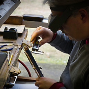 David Schapani uses a caliper to measure flute components in thousandths of an inch.