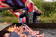 12 SEPTEMBER 2020 - DES MOINES, IOWA: MIKE ROWLEY wore a replica of a US Army uniform from the War of 1812 during a flag retirement ceremony at Glendale Cemetery in Des Moines. About 10 volunteers came to the cemetery Saturday morning to properly dispose of about 4,000 American flags. The flags had flown over veterans' graves, local businesses, and state offices. The US Flag Code calls for used American flags to be respectfully disposed of in a fire.     PHOTO BY JACK KURTZ