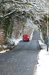 © Licensed to London News Pictures. 14/01/2015. A Royal Mail van drives through a snowy archway on the B4520  'Brecon Road'. Snow fell last night in Mid-Wales and cold temperatures have prevented the snow from melting. Builth Wells, Powys , Wales, UK. Photo credit: Graham M. Lawrence/LNP