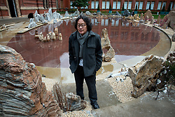 © Licensed to London News Pictures.31/10/2013. London, UK. Xu Bing, Chines artist stands by the lake of he John Madejski Garden at V&A Museum, where his new installation is shown. Travelling to the Wonderland inspired by the classic Chinese fable Tao Hua Yuan (The Peach Blossom Spring). The V&A invited Xu Bing to create a major new work to coincide with the Museum's forthcoming exhibition, Masterpieces of Chinese Painting 700 – 1900.Photo credit : Peter Kollanyi/LNP