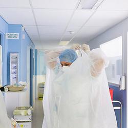 Extrait du reportage au long cours Covid19 ce que veut dire être soignant publié aux éditions Byakko en décembre 2020. <br /> Suivi du quotidien des équipes de l'hôpital d'instruction des armées Bégin de Saint-Mandé pendant la première vague de l'épidémie de coronavirus en France. Pendant 3 mois, la photographe a partagé le quotidien des personnels de garde : infirmières, aide-soignants, médecins, manipulateurs-radio, etc. au sein des différents services consacrés aux victimes du Covid-19. <br /> <br /> Avril-Juillet 2020 / Saint-Mandé (94) / FRANCE<br /> <br /> Toujours le même rituel avant d'entrer dans la chambre d'un patient suspecté d'être porteur du coronavirus : vérifier les équipements de tête (masque FFP2, charlotte, lunettes) et revêtir une surblouse jetable doublée d'un tablier plastique. Quand des tensions sur l'approvisionnement en équipement de protection sont apparues, le personnel soignant laissait à l'entrée de la chambre d'un patient sa surblouse à usage unique pour faire durer le stock tout en évitant les contaminations croisées. <br /> <br /> Découvrir le livre Covid19 ce que veut dire être soignant https://byakko.fr/boutique/livre-covid19-ce-que-veut-dire-etre-soignant/<br /> Voir plus de photos de ce reportage (55 photos) https://sandrachenugodefroy.photoshelter.com/gallery/2020-04-Covid19-ce-que-veut-dire-tre-soignant/G0000_uUmPCIj7oo/C0000yuz5WpdBLSQ