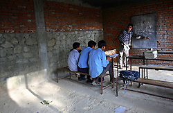 Chakraman Shreshta Balami, 28, teaches at the one school inside Kagati Village, Kathmandu Valley, Nepal on Jan. 31, 2007. This high school class is barely attended because most of the students are already married and no longer attend classes. Although the uncle of a recent child bride, Chakraman has worked for years with a group of other men in the village to stop the practice. The Kagati village, a Newar community, is most well known for its propensity towards child marriage. Many Hindu families believe blessings will come upon them if marry off their girls before their first menstruation.