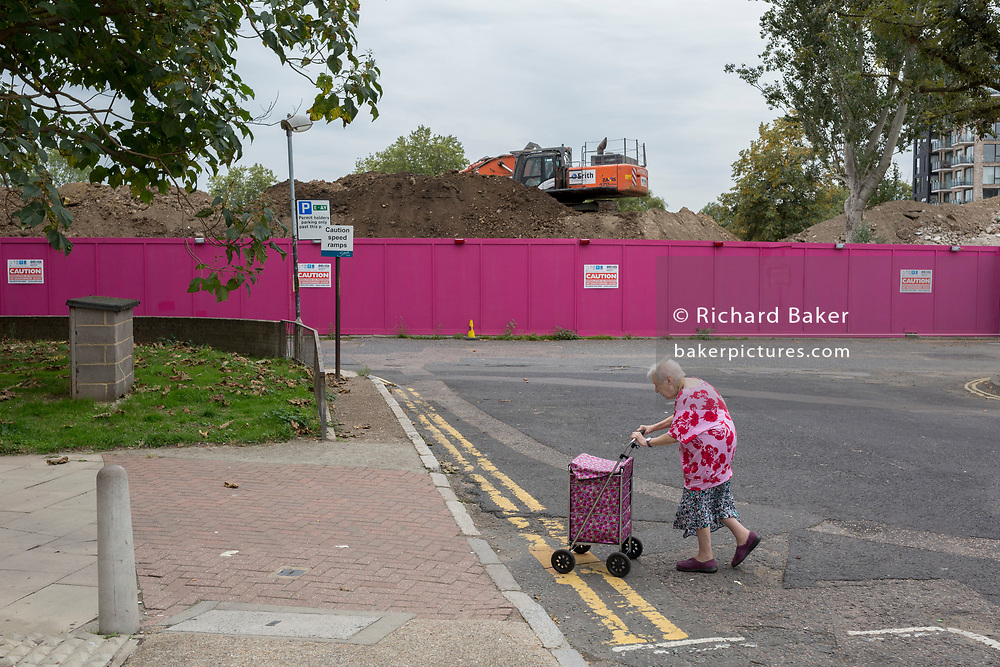 """An elderly lady walks slowly with her shopping trolley across a road on the Aylesbury Estate, on 4th September 2018, in Southwark, London, England. The Aylesbury Estate contained 2,704 dwellings in approximately 7500 residents and built between 1963 and 1977 and for decades it was seen as a symbol of the failure of British social housing. There were major problems with the physical buildings on the estate and the poor perception of estates in Britain as a whole have led to the Aylesbury Estate gaining the title of """"one of the most notorious estates in the United Kingdom. Demolition is in progress for the regeneration of the Aylesbury Estate to consist of 3,500 new homes, 50% of which, according to Southwark council, will be affordable."""