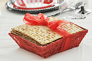Matzo wrapped with a ribbon on a Jewish Passover table set with disposable plastic dishes